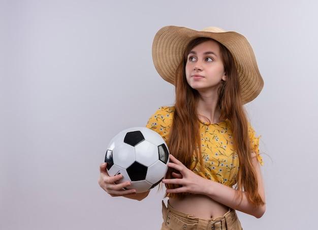 Seriamente cercando giovane ragazza che indossa il cappello tenendo il pallone da calcio guardando il lato sinistro su uno spazio bianco isolato con copia spazio