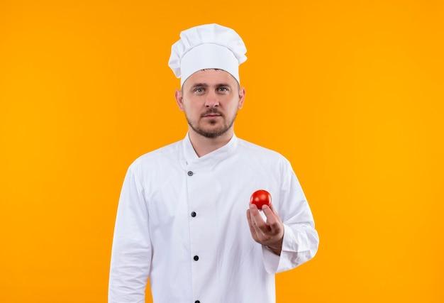 Seriamente guardando giovane bello cuoco in uniforme del cuoco unico che tiene pomodoro e guardando isolato su spazio arancione