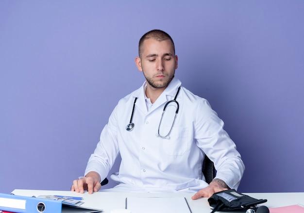 Серьезно выглядящий молодой мужчина-врач в медицинском халате и стетоскопе сидит за столом с рабочими инструментами, кладет руки на стол и смотрит на стол, изолированный на фиолетовой стене