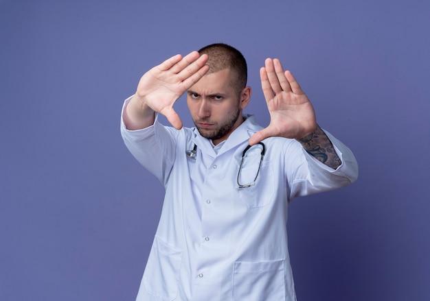Seriamente guardando giovane medico maschio che indossa veste medica e stetoscopio intorno al collo allungando le mani verso la parte anteriore isolata sul muro viola