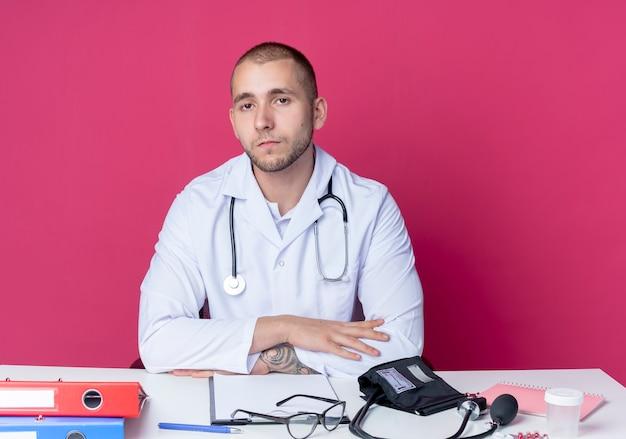 Guardando seriamente giovane medico maschio che indossa veste medica e stetoscopio seduto alla scrivania con strumenti di lavoro che mette le mani sulla scrivania guardando davanti isolato sul muro rosa
