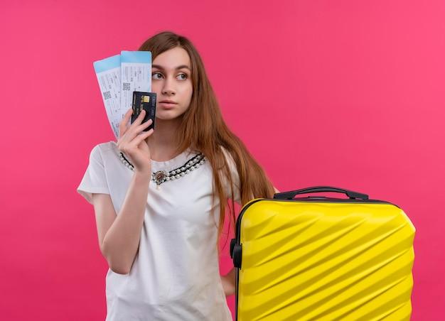 Серьезно выглядящая молодая девушка-путешественница держит билеты на самолет, кредитную карту с чемоданом на изолированном розовом пространстве