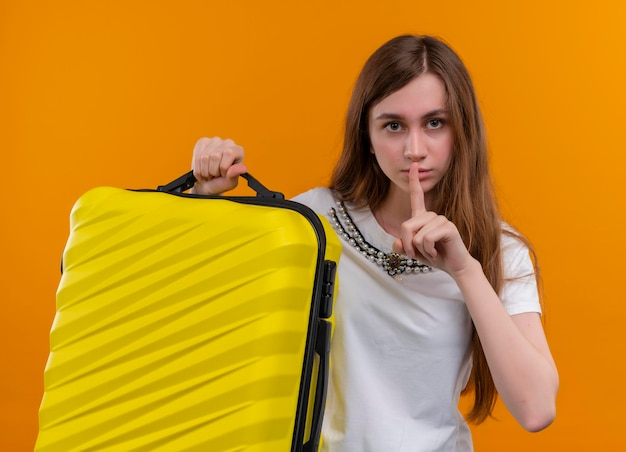 Серьезно выглядящая молодая девушка-путешественница держит чемодан и жестикулирует в изолированном оранжевом пространстве