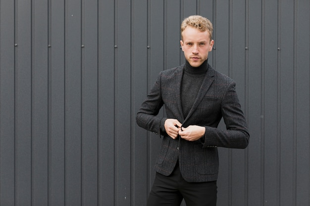 Seriously man in black near a gray wall