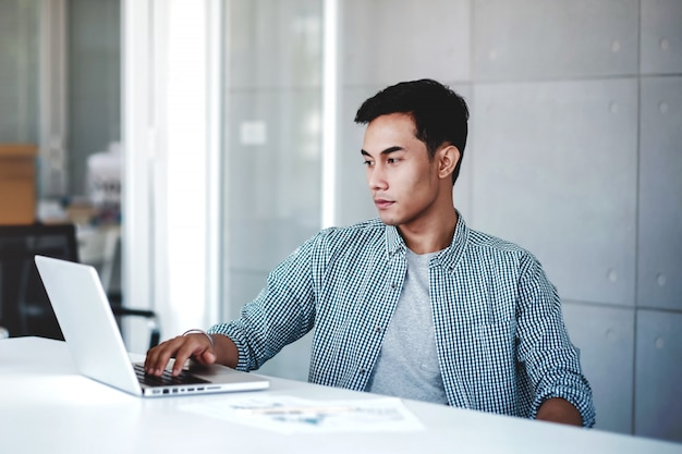 Seriously young businessman working on computer laptop in office.