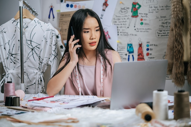 Seriously young designer talking with smartphone while use laptop computer to checking together