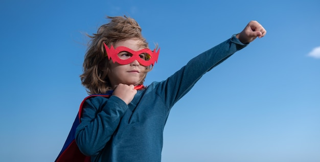 슈퍼히어로 의상을 입은 seriuos 아이. 푸른 여름 하늘 배경에 슈퍼 영웅 아이입니다. 야외에서 즐거운 시간을 보내는 아이. 키즈 파워 컨셉입니다.