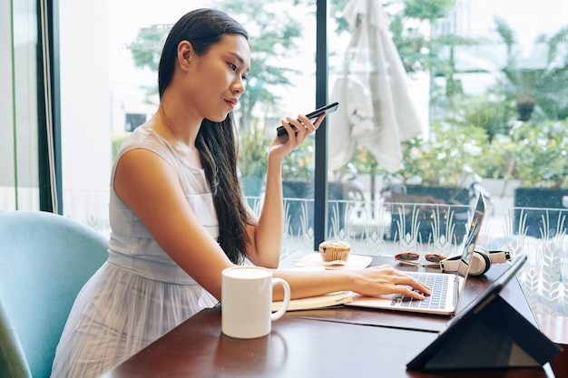 Seriuos pretty young asian woman with smartphone in hands anwering e-mails on laptop when sitting at cafe table with cup of coffee