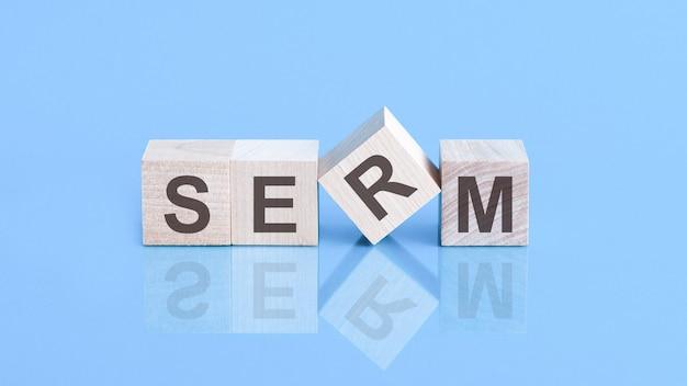 Слово serm состоит из деревянных кубиков, лежащих на синем столе, бизнес-концепция. serm - сокращение от search engine reputation management.