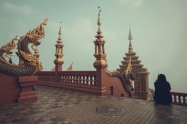 Змеиный король или король статуи наги в храме женщина таиланда, сидящая на лестнице.