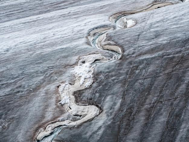 氷河の曲がりくねった断層、氷河の雪に覆われた斜面の氷の危険な亀裂。氷河からの氷のひび割れや引っかき傷がある氷の壁の最小限の自然な背景。