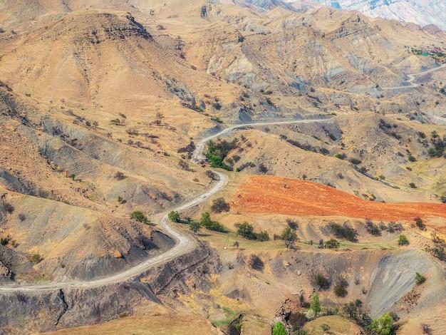 赤い谷を渡る曲がりくねった道。航空写真。