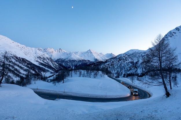 曲がりくねった道冬のベルニナ峠のイタリアとスウェーデンのアルプス山脈の雪