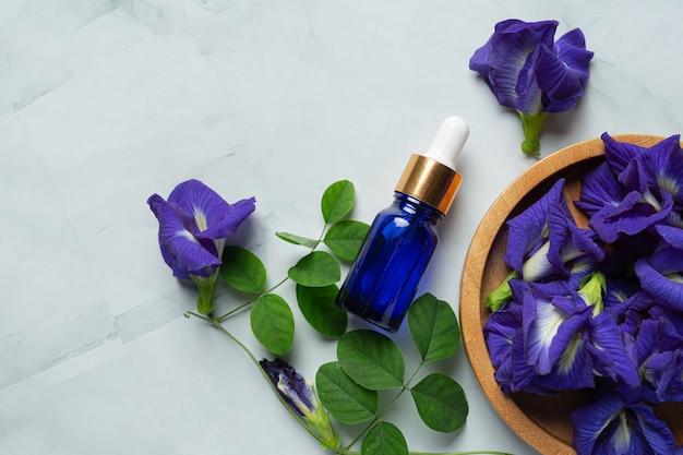 Bottiglia di siero di olio di fiori di pisello farfalla messo su sfondo di marmo bianco
