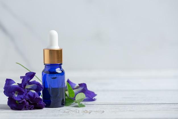 Bottiglia di siero di olio di fiori di pisello farfalla messa sul pavimento di legno bianco