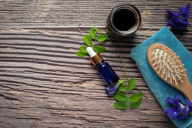 木製の背景に置かれた蝶エンドウ豆フラワーオイルの血清ボトル