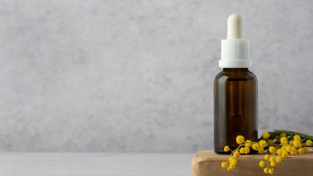 Bottiglia di siero e pianta con copia spazio