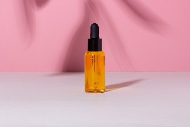 Флакон с сывороткой с капельницей с тенями на фоне. косметический спа-продукт и пипетка для ухода за кожей