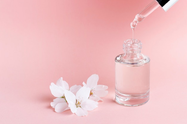 Serum and dropper on a pink background close-up, natural cosmetics concept