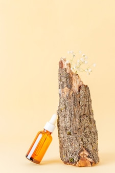 Serum or essential oils in brown glass bottle with pipette and wood log on light yellow background
