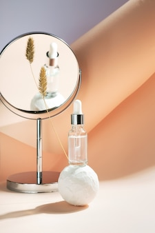 Serum in glass bottle with dropper on white ball with plant branch