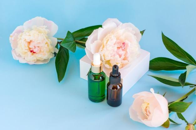 Стеклянные бутылки для сыворотки с пипеткой и красивым цветком пиона на пастельно-синем фоне. естественная органическая косметическая концепция спа.