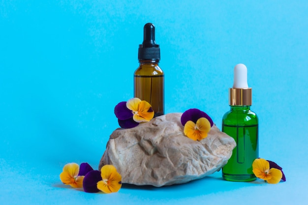 파란색 배경에 피펫과 아름다운 비올라 꽃이 있는 혈청 유리병. 천연 유기농 스파 화장품 컨셉입니다. 전면보기.