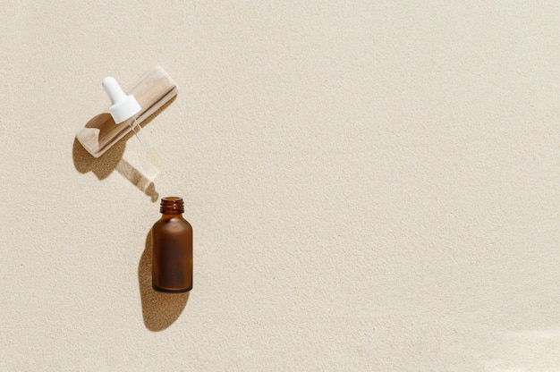 Serum or liquid collagen dropper bottle on sand background with sunlight shadow from palm leaves