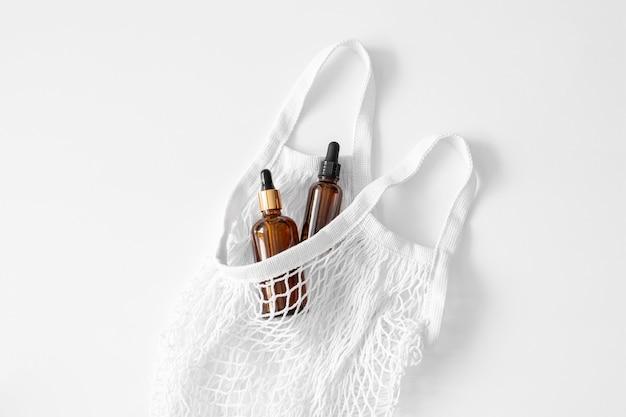 세럼, 오일, 산, 갈색 점적기 유리에 로션, 메쉬 백에 피펫이 흰색으로 평평하게 놓여 있습니다. 스파 제품. 재사용이 가능한 친환경 쇼핑백. 유기농, 천연 화장품. 뷰티, 스킨케어. 제로 폐기물.