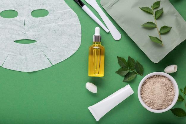 Сыворотка-масло и тканевая косметическая маска для лица с набором косметической глиняной маски, кисточка-шпатель, увлажняющий крем. косметические спа-процедуры для ухода за кожей лица, косметология на зеленом фоне с листьями.