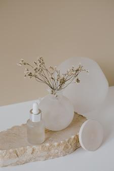 피펫이 포함 된 세럼 오일 유리 병, 중성 파스텔 베이지에 꽃이있는 스톤