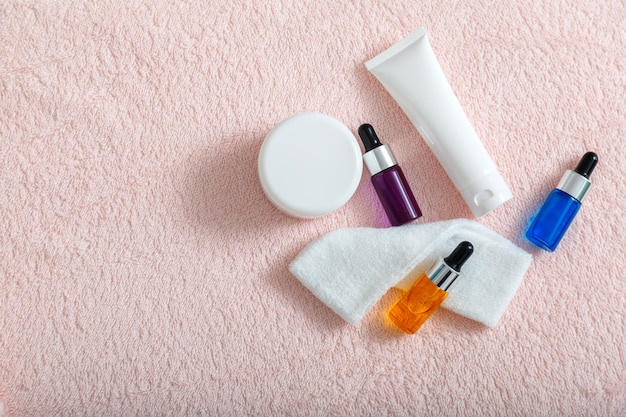 血清オイル保湿クリーム マスク コットン パッド スキンケア化粧品家庭用またはサロン美容師ケア化粧品スキン コスメトロジー スパまたはコピー スペース付きのピンクのタオルのトップ ビュー