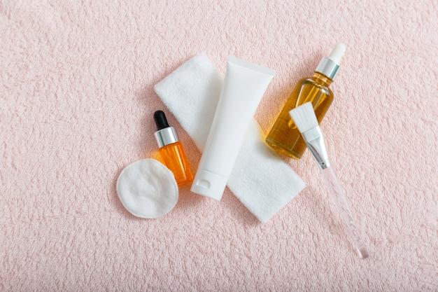 ホームまたはサロンの美容師ケアのための血清オイル保湿クリームスキンケア化粧品。スキンコスメトロジースパやデイリーユースのコスメ。フェイシャルマスクを適用するためのコットンパッドブラシ。ピンクのタオルの上面図。