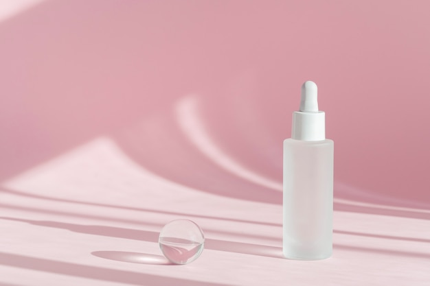 Serum oil with collagen and peptide in white transparent bottle with dropper on pink decor background