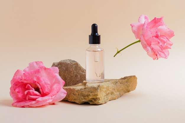 Сыворотка или косметическая жидкость, масло на камне рядом с цветком розы