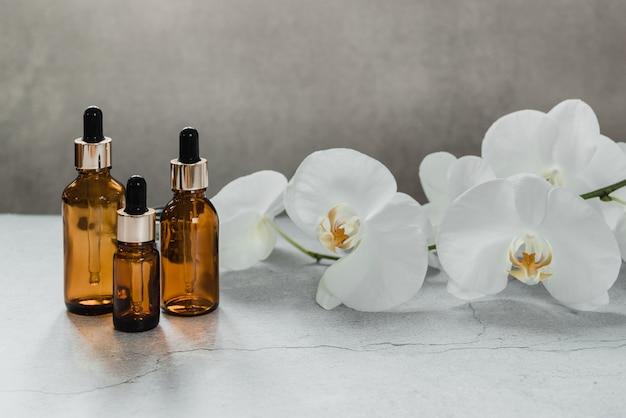 난초 꽃이 배경에 있는 세럼 또는 에센셜 오일 병 모형, 천연 미용 화장품 피부 제품, 스포이드 병에 든 홈 스파