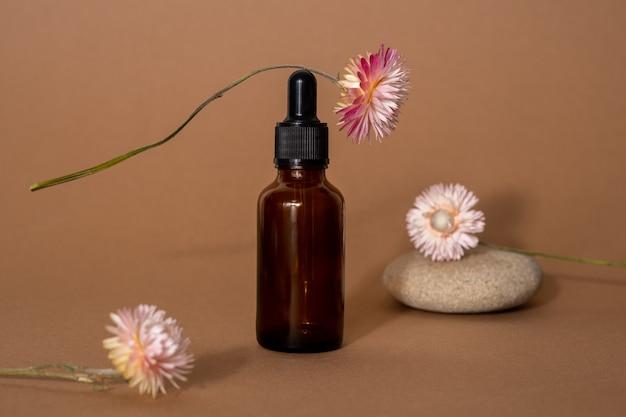 베이지 색 표면에 피펫, 돌 및 말린 꽃이있는 갈색 유리 병의 세럼 또는 에센셜 오일