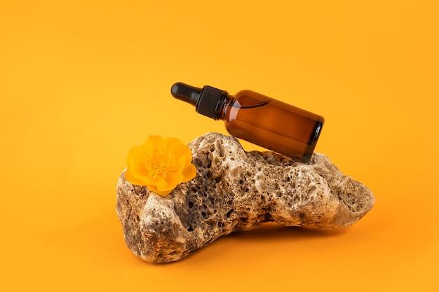 오렌지 배경에 돌과 꽃에 갈색 유리 스포이드 병에 세럼 또는 에센셜 오일. 천연 유기농 스파 화장품 개념 전면 보기입니다.