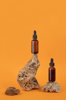 石、オレンジ色の背景に茶色のガラススポイトボトルの血清またはエッセンシャルオイル。ナチュラルオーガニックスパ化粧品コンセプト正面図。