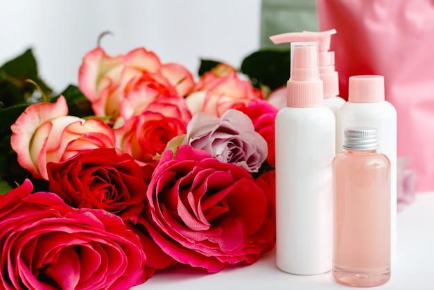 흰색 테이블 꽃 배경에 세럼, 비누, 오일. 꽃 레드 핑크 장미 천연 유기농 미용 제품. 스파, 스킨 케어, 목욕 바디 트리트먼트. 장미 목업이 있는 분홍색 플라스틱 화장품 병 세트.