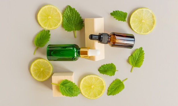Serum with vitamin c. lemon essential oil. brown and green glass bottle with a pipette, slices of lemon with mint leaves on a gray background. health and beauty concept. organic natural cosmetics.