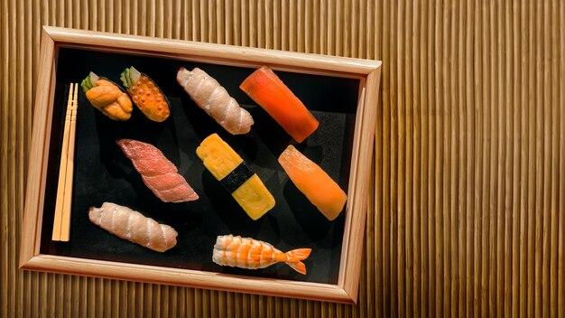 背景の竹の木の木製プレートに寿司日本料理を提供します