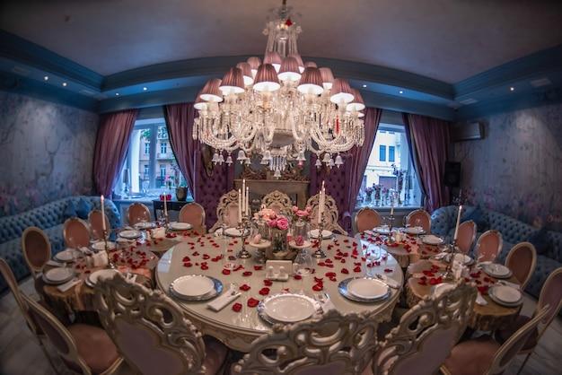 Обслуживается банкетный круглый стол. ресторан. украшенный стол на свадьбу.