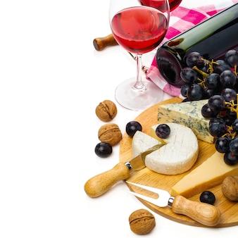 白いテーブルに分離されたチーズとワインを提供
