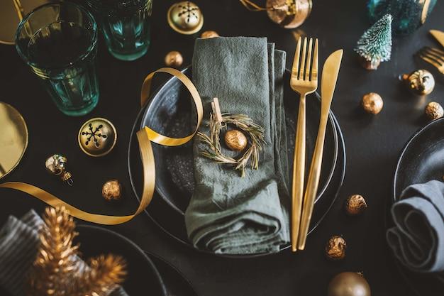 황금색 데코가 있는 어두운 색조의 크리스마스 테이블 설정을 제공합니다.