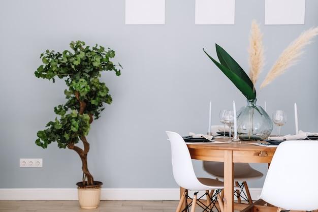 Обеденный стол в современной скандинавской кухне с комнатными растениями и белыми рамками на стене.