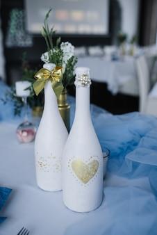 ブルーホワイトのウェディングバンケットテーブルにご利用いただけます。結婚式の装飾。白い皿の上の花と青いナプキン。ゴールデンボトルは花瓶です。装飾されたシャンパンのボトル。