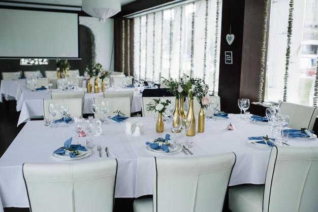 ブルーホワイトのウェディングバンケットテーブルにご利用いただけます。結婚式の装飾。白い皿の上の花と青いナプキン。ゴールデンボトルは花瓶です。