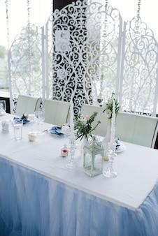 블루 화이트 웨딩 연회 테이블 제공. 웨딩 장식. 하얀 접시에 꽃과 푸른 냅킨입니다. 비쳐 아치.