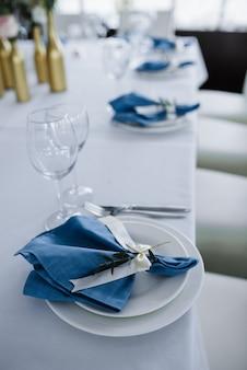 블루 화이트 웨딩 연회 테이블 제공. 웨딩 장식. 하얀 접시에 꽃과 푸른 냅킨입니다.